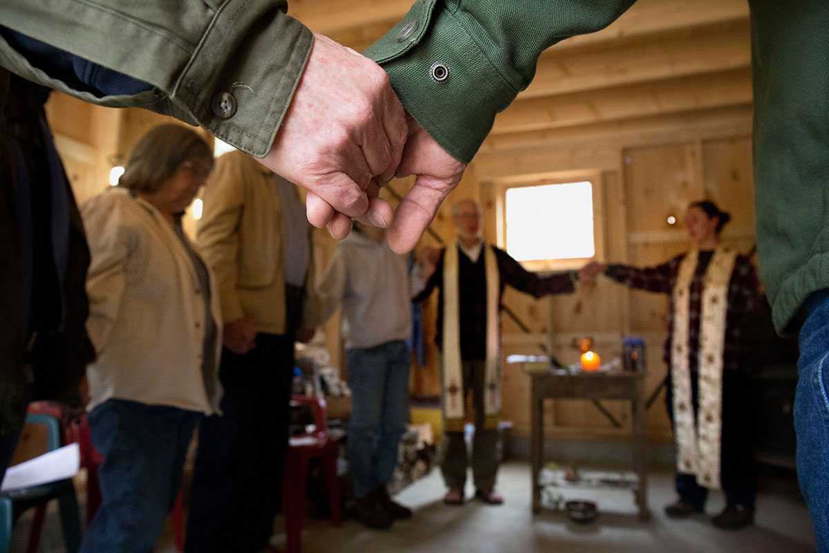 Rick Coffin, of Barstead, left, and West Jones, of Loudon, hold hands and sing a hymn with others during the afternoon service at Church of the Wood.