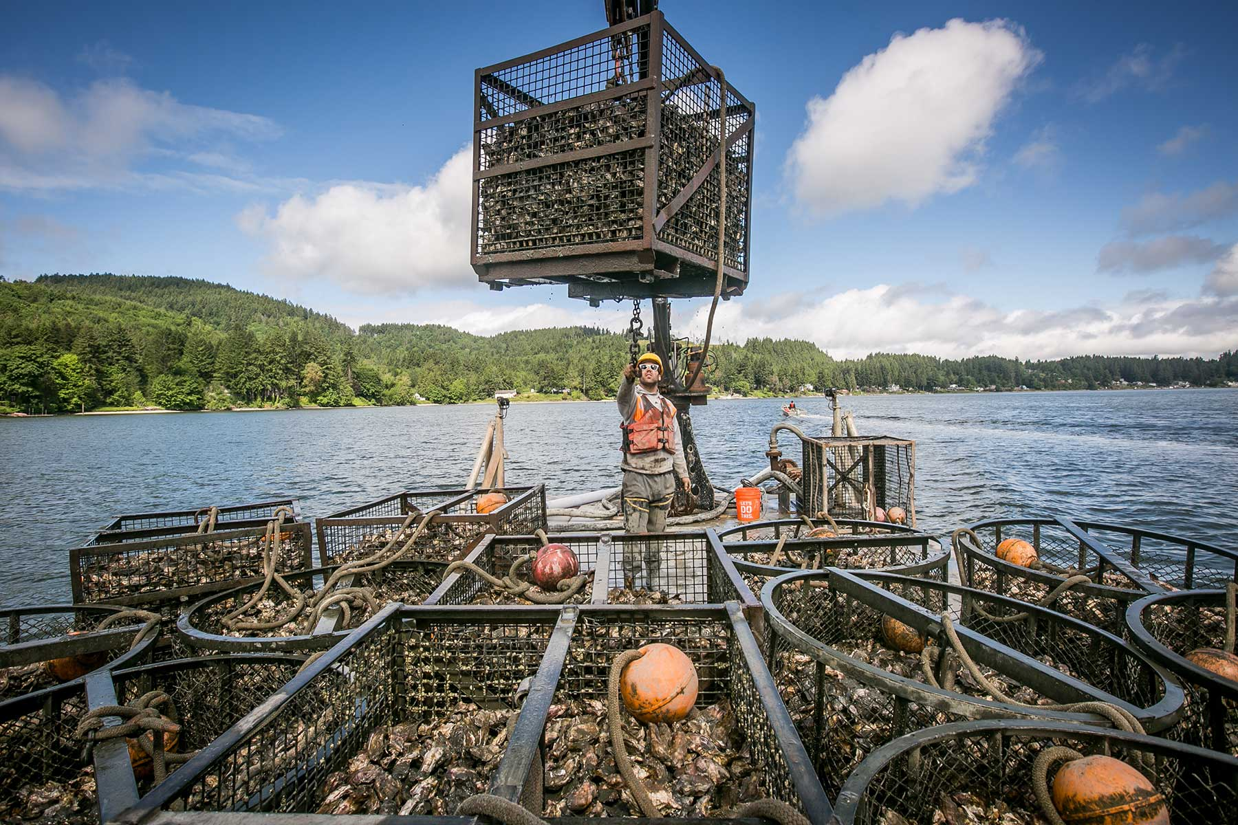 Adam Kravitz works on a boat to transplant oysters from one area to another in Mud Bay.