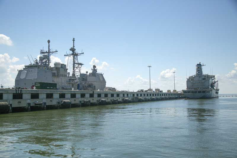 Caption: Ships docked at a double decker pier at Naval Station Norfolk (Alex Chancey)