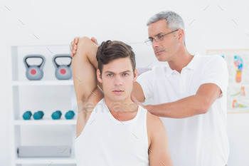 Doctor stretching a young man arm in medical office 484340