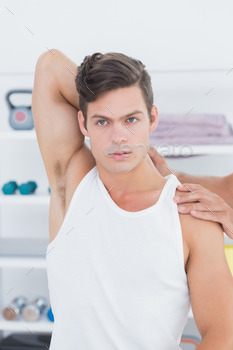 Doctor stretching a young man arm in medical office 484339