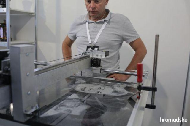 Демонстрация технологии печати портретов для надгробных памятников на выставке современной похоронной культуры RIP EXPO в Киеве, 26 июня 2021 года