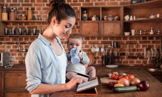 Person shopping for secondhand reusable nappies on tablet while holding baby