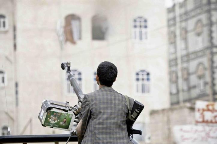 A Houthi fighter holds a weapon as he looks at smoke rising from a building in Sana'a