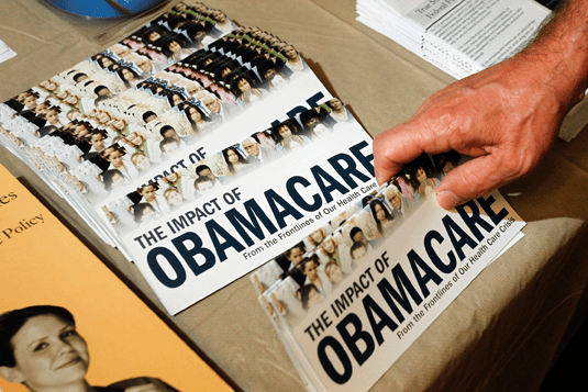 """A Tea Party member reaches for a pamphlet titled """"The Impact of Obamacare"""", at a rally in Littleton, N.H., in this Oct. 27, 2012 photo. REUTERS/Jessica Rinaldi//Files"""