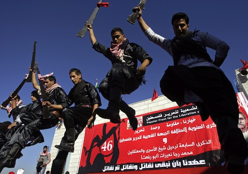 Palestinians dance at a rally marking the 46th anniversary of the founding of the Popular Front for the Liberation of Palestine
