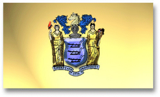 The State flag of New Jersey is buff colored. The state coat of arms is emblazoned in the center. The shield has three plows with a horse's head above it. Two women represent the goddesses of Liberty and Agriculture. A ribbon at the bottom includes t