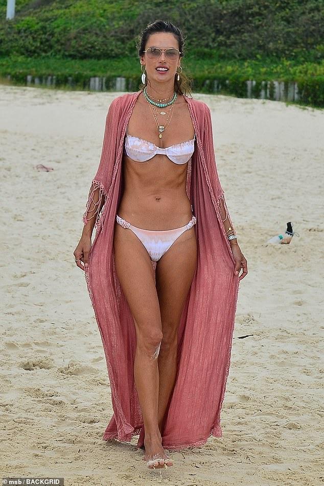 Playa: Alessandra Ambrosio hizo alarde de su impresionante figura en un diminuto dos piezas blanco y rosa mientras modelaba los últimos diseños de su línea de trajes de baño, Gal Floripa, el viernes.