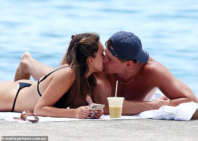 ¿Nuevo novio?  La finalista de la licenciatura Bella Varelis (izq.) Disfrutó de un beso en los labios con el fotógrafo Will Stokoe (der.) Mientras se quitaba un diminuto bikini negro en Balmoral Beach el domingo.