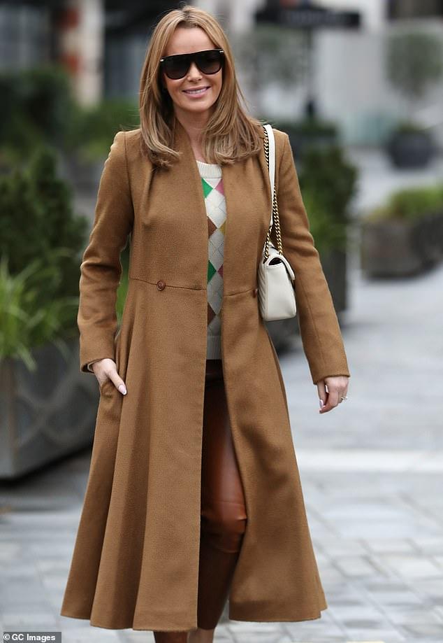 Aspecto atemporal: Amanda Holden lucía increíblemente elegante el martes mientras lucía un abrigo color camel y una sudadera de rombos cuando terminó de grabar su programa Heart FM.
