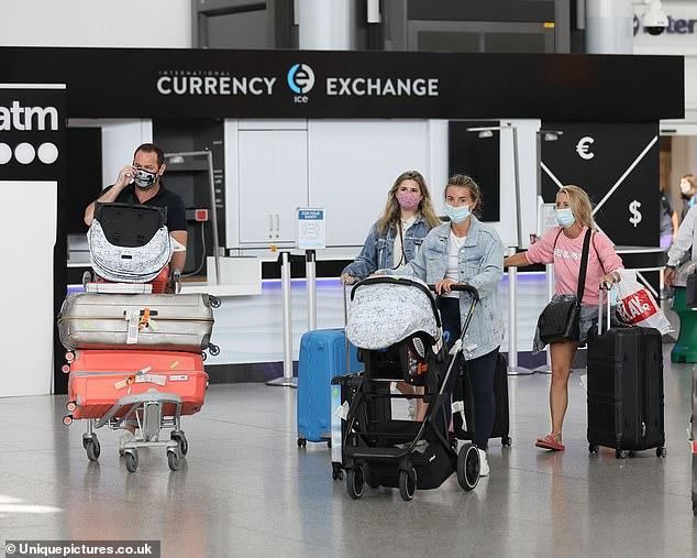 De camino a casa: Dani Dyer (segunda desde la derecha) llevó el cochecito de su hijo Santiago a través del aeropuerto cuando aterrizó en el Reino Unido el sábado con su padre Danny, su madre Jo (a la derecha) y su hermana Sunnie (segunda desde la izquierda) siguiendo su sol. empapado viaje a españa