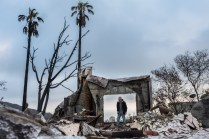 """Mike is looking through the burned out remains of what used be his front door, in Latiogo canyon Malibu CA. Mike stayed to try and save his home during the Woolsey fire, He fought the fire together with his wife until they realized there was nothing they could do, by this time the house was engulfed in flames and it was hard for them to breathe. Mike talked about the moment of sadness of leaving their home knowing they were going to lose it, running through flames to find a way out. He built this house 30 years ago he said with an exhausted look on his face, """" at 71 years old I probably still have it in me to build one more house """""""