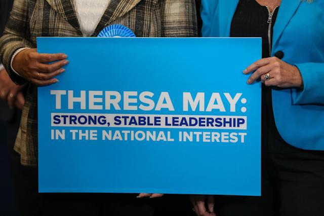 Attendees hold a placard bearing the slogan 'Theresa May: Strong, Stable Leadership in the national interest' at a Conservative Party general-election campaign event in Norwich, U.K., on Wednesday, June 7, 2017. Maysaid she'd be willing to tear up human-rights legislation to combat terrorism in a move the Labour opposition said was an attempt to distract from her cuts to police, as security dominated the closing stages of the U.K. election campaign. Photographer: Chris Ratcliffe/Bloomberg