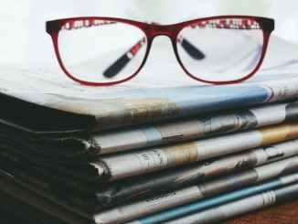 red framed eyeglasses on newspapers