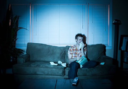 Young man watching tv, crying