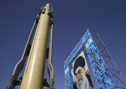 A Ghadr-F missile is displayed next to a portrait of Iranian Supreme Leader Ayatollah Ali Khamenei at a Revolutionary Guard hardware exhibition