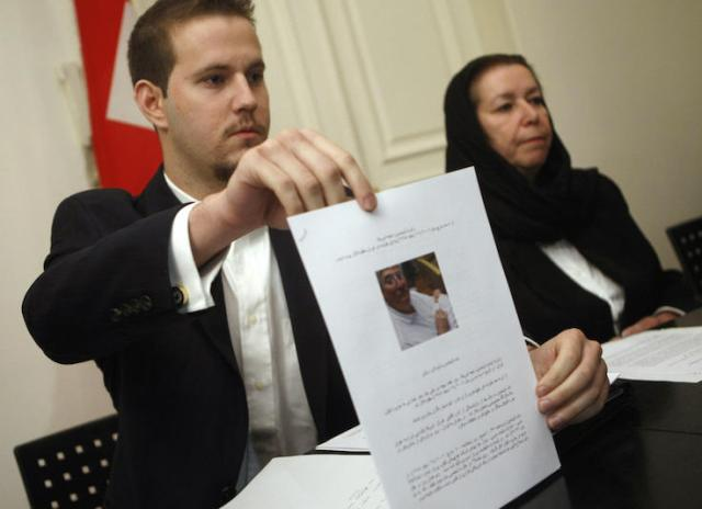 Daniel Levinson (L) shows a picture of his father, ex-FBI agent Robert Levinson during a press conference