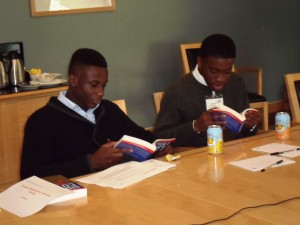 ACD Students Andrew Conteh and Sam Adefioye, skim Stephen Covey's book during a break