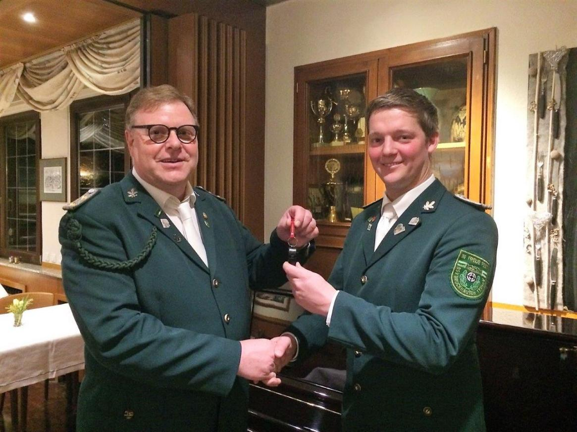 Alt-Hauptmann Hans-Werner Kratz überreicht die Amtsinsignien an seinen Nachfolger Dominik Friebe.