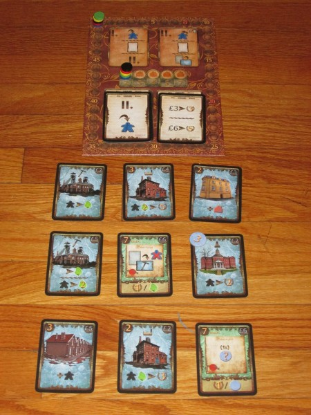 Here is a game set up for five players. The board tracks the score, the future and active event, the residence track, and which phase each player is in. The 3x3 grid is the market, where players will place their workers to activate cards.
