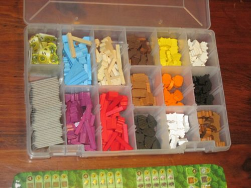 The box is full of wooden and cardboard bits. I've organized mine in a plastic storage box for easier set up, but the game comes with an ample supply of plastic bags.