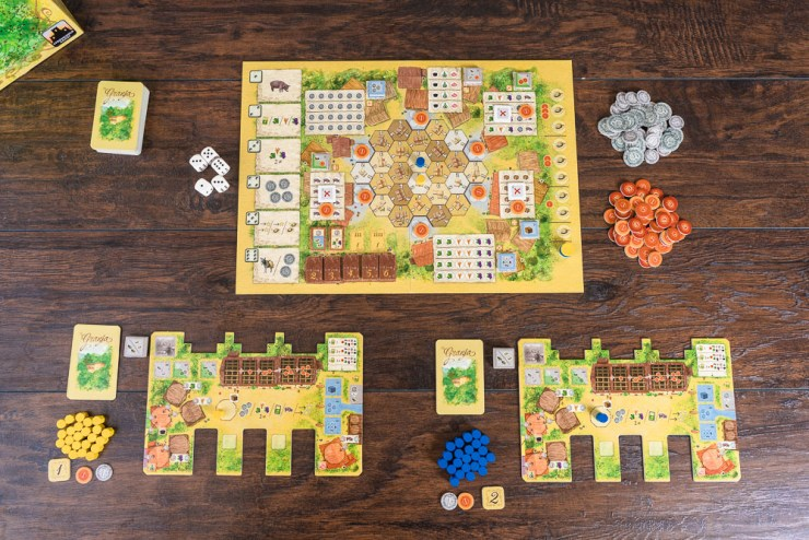 Setup for 2 players includes a farm board, a hand of cards, a coin, a trade good, and a victory point.