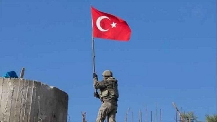 جندي يرفع العلم التركي على الأراضي السورية بعد السيطرة عليها 1