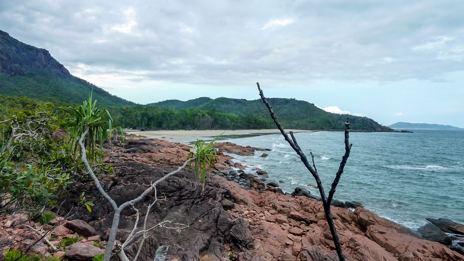this is a photo of red boulders on a beach of hinchinbrook island