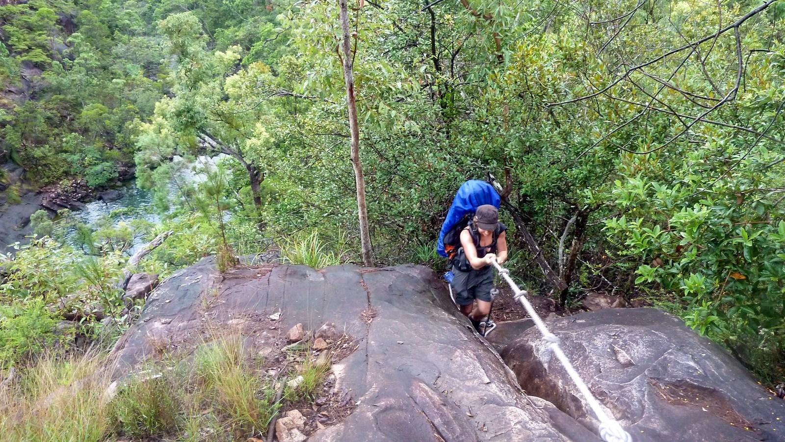 a photo of a hiker climbing on a rope on hinchinbrook island.