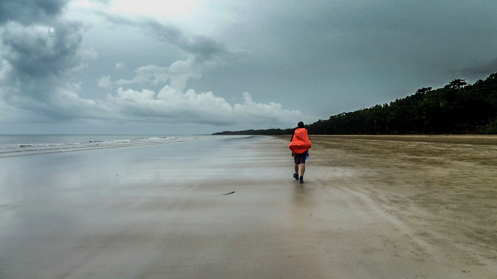 a photo of a hiker on a beach on hinchinbrook island with clouds in the background.