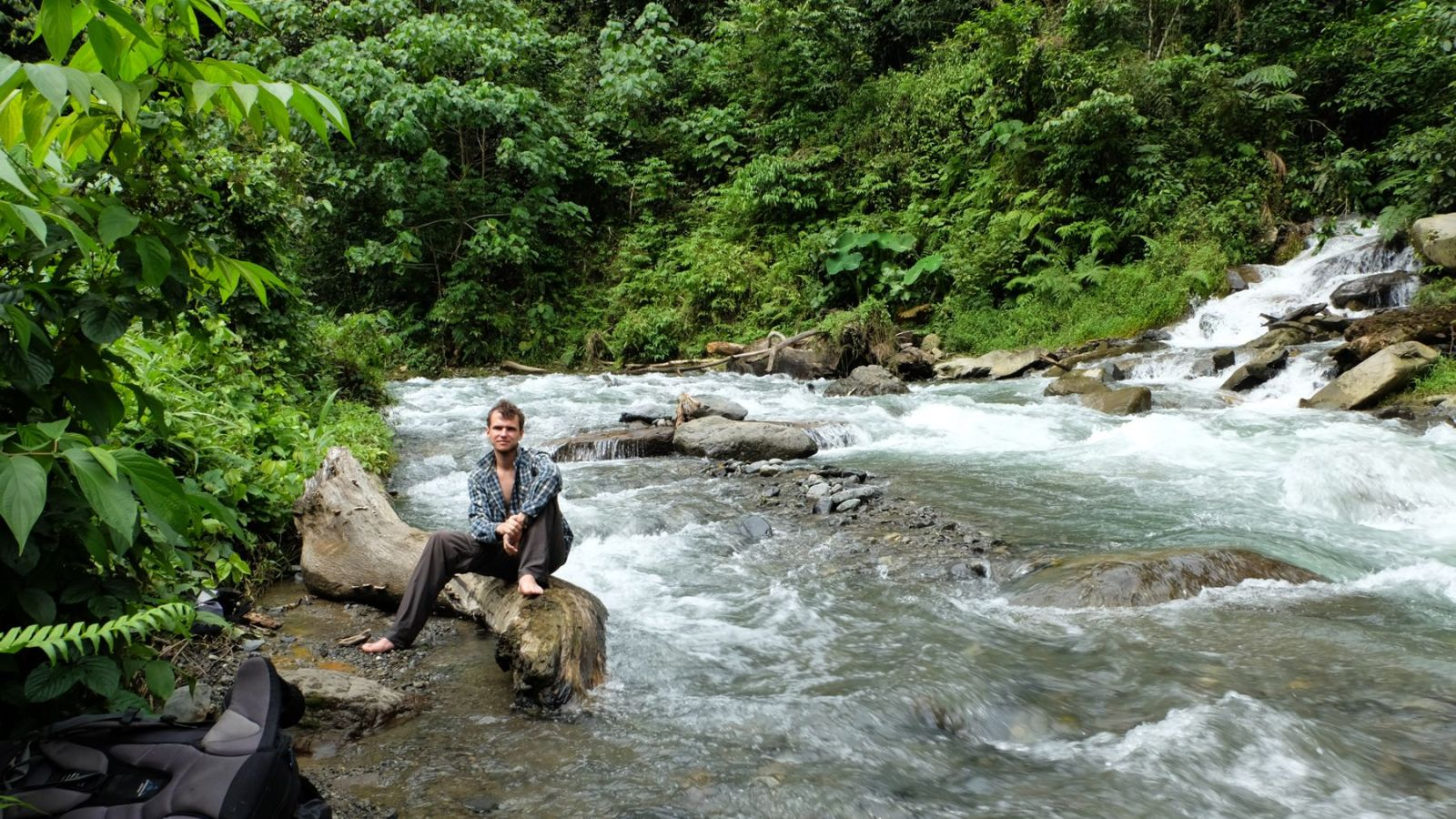 a photo of a hiker sitting on a rock next to a river in gunung leuser national park.
