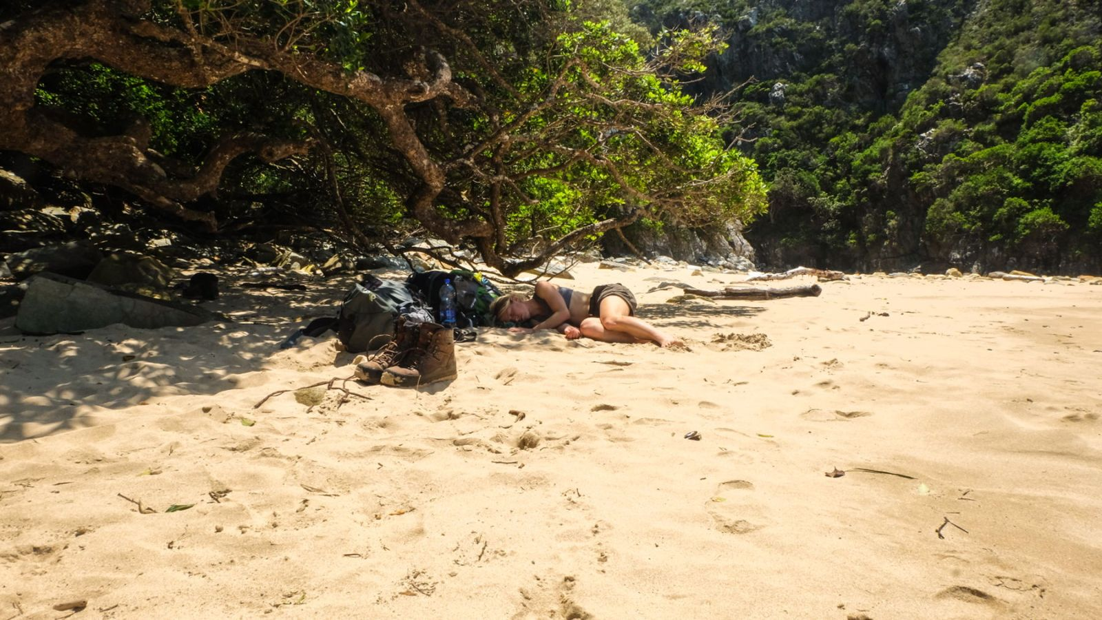 this is a photo of a hiker sleeping on a beach along the otter trail