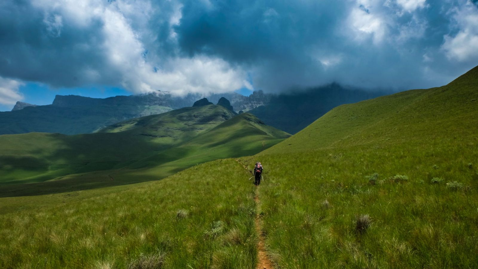 photo of the mountains in the drakensberg with a hiker in the distance