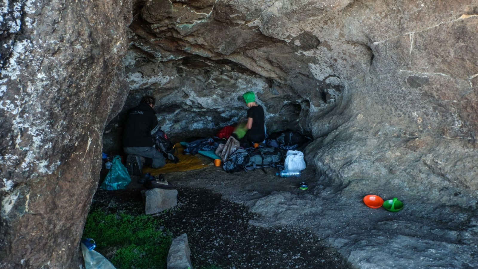 photo of a cave in the drakensberg mountains with a hiker and camping gear on the ground