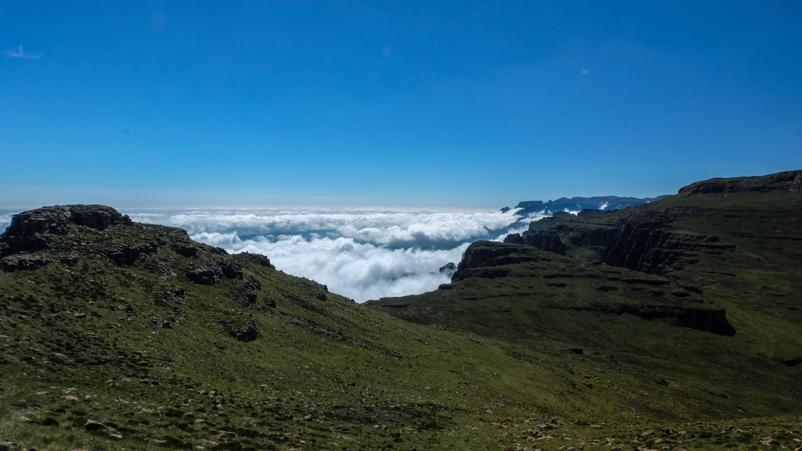 photo from a mountain plateau above the clouds with the drakensberg mountains in the background