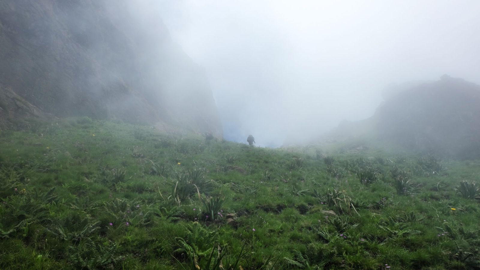 photo of a foggy trail in the drakensberg mountains with hiker in the distance