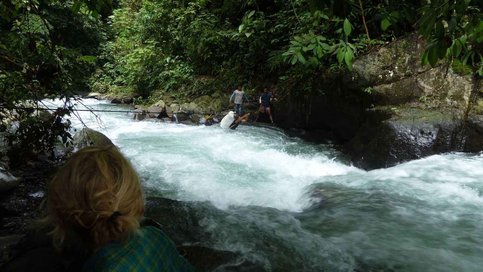 a photo of a porter in gunung leuser national park crossing a river on a rope.