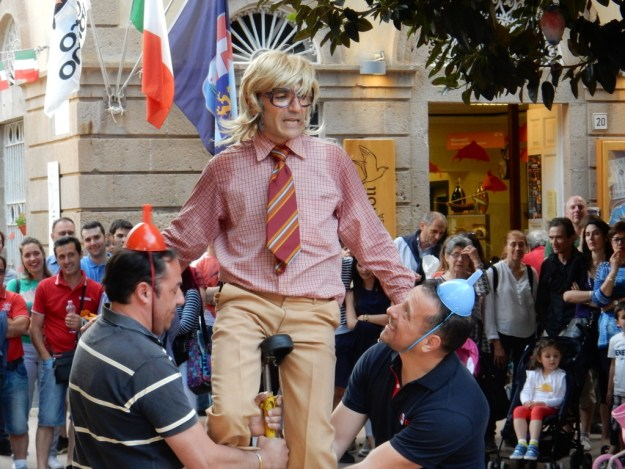 Clown on unicyce entertains in the town square during Giro Tonna