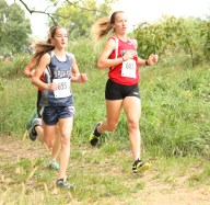 Freshman Jadyn Dorn stays in stride with this Wamego runner during the girls' cross country race on Thursday, October 4, at the Sabetha Golf and Country Club.