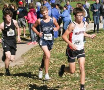 Sophomore Kaden Dillon pushes himself up this hill following closely behind this Marysville runner during the 3A Regional Cross Country meet on Saturday, October 20, in Sabetha.