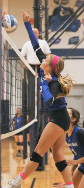 Junior Nikki Kuenzi hits it through the blockers hands during league action with Hiawatha on Tuesday, October 16.