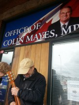 Tuning guitar in front of Colin Mayes (Conservative MP)'s office