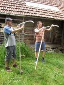 Flaviu instructs Graham on the finer points of scythe maintenance