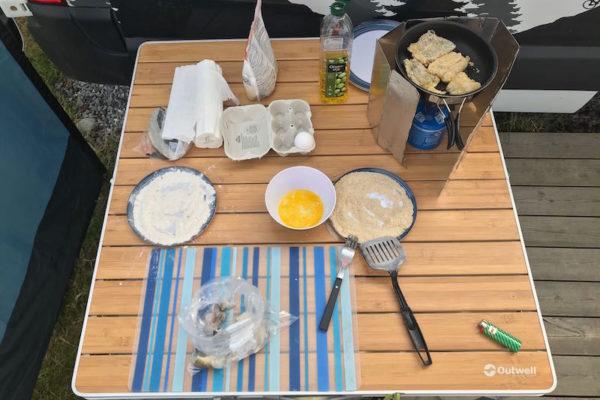 Fröhliches Dorsch-Panieren auf dem Campingplatz in Leirvik. Der Sonnenschein täuscht jedoch: frische 11 Grad und 'en stiv bris'. Der Camping ist übrigens voll von trinkfreudigen Pétanque-Spielern, welche um die Norwegische Meisterschaft kämpfen.