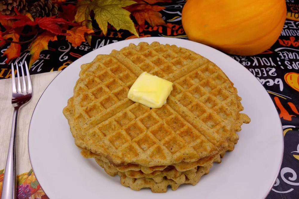 A stack of homemade Paleo pumpkin waffles on a white plate topped off with grass-fed butter