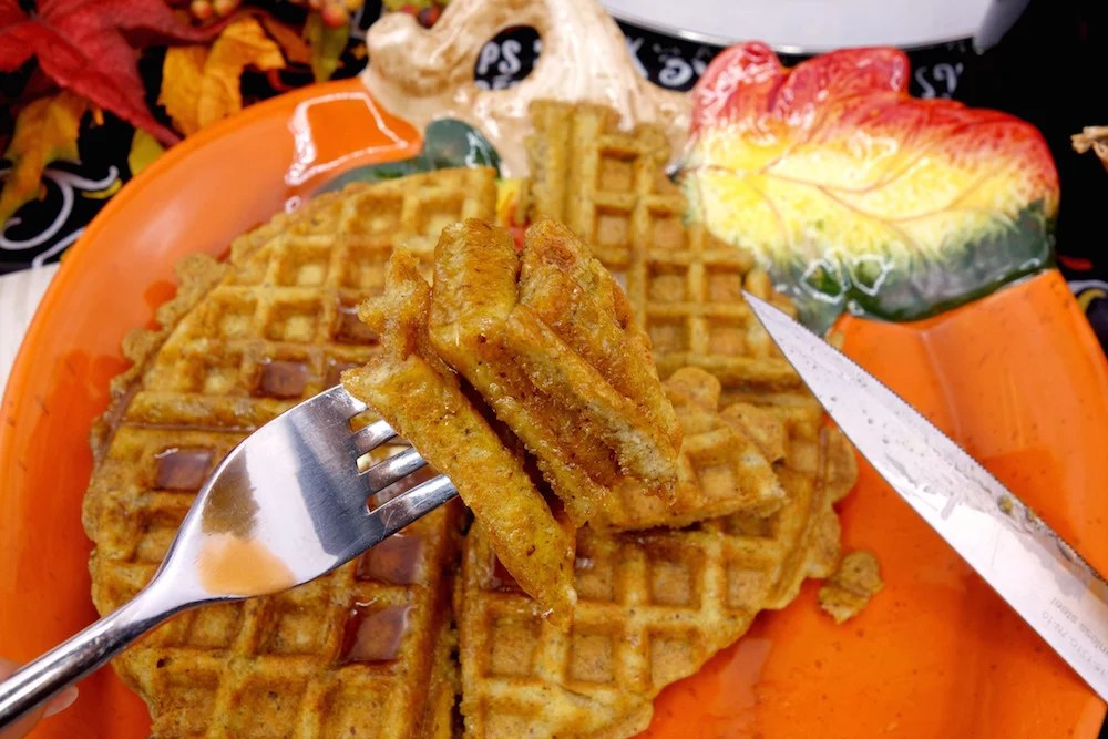 A fork full of homemade Paleo pumpkin waffles with maple syrup, with more Paleo pumpkin waffles in the background
