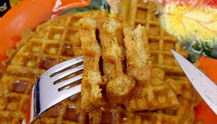 Close up view of a fork full of homemade Paleo pumpkin waffles with maple syrup, with more Paleo pumpkin waffles in the background
