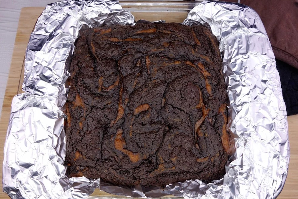Freshly baked homemade fudgy Paleo pumpkin swirl brownies in a 8x8 baking dish lined with foil