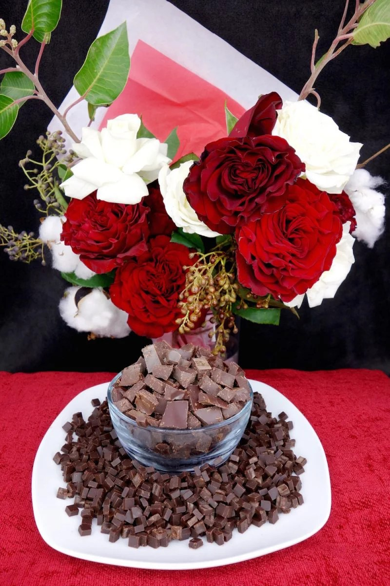 Homemade Paleo chocolate chips on a white plate, encircling a bowl of Paleo chocolate chunks with a bouquet of red and white roses and cotton in the background