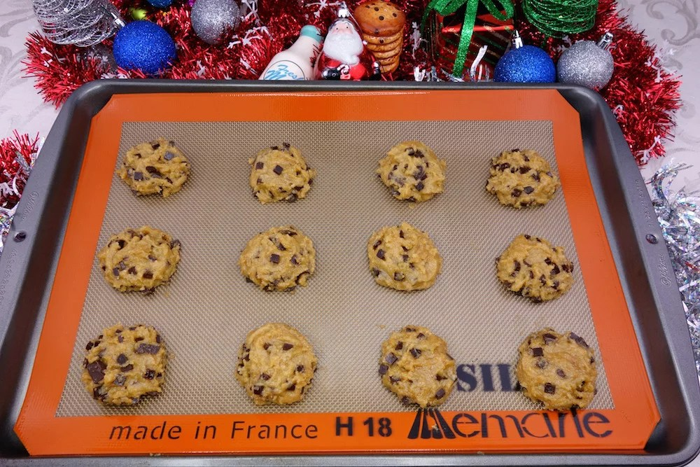 homemade soft and chewy Paleo chocolate chip cookies dough on a silpat with Christmas decorations in the background